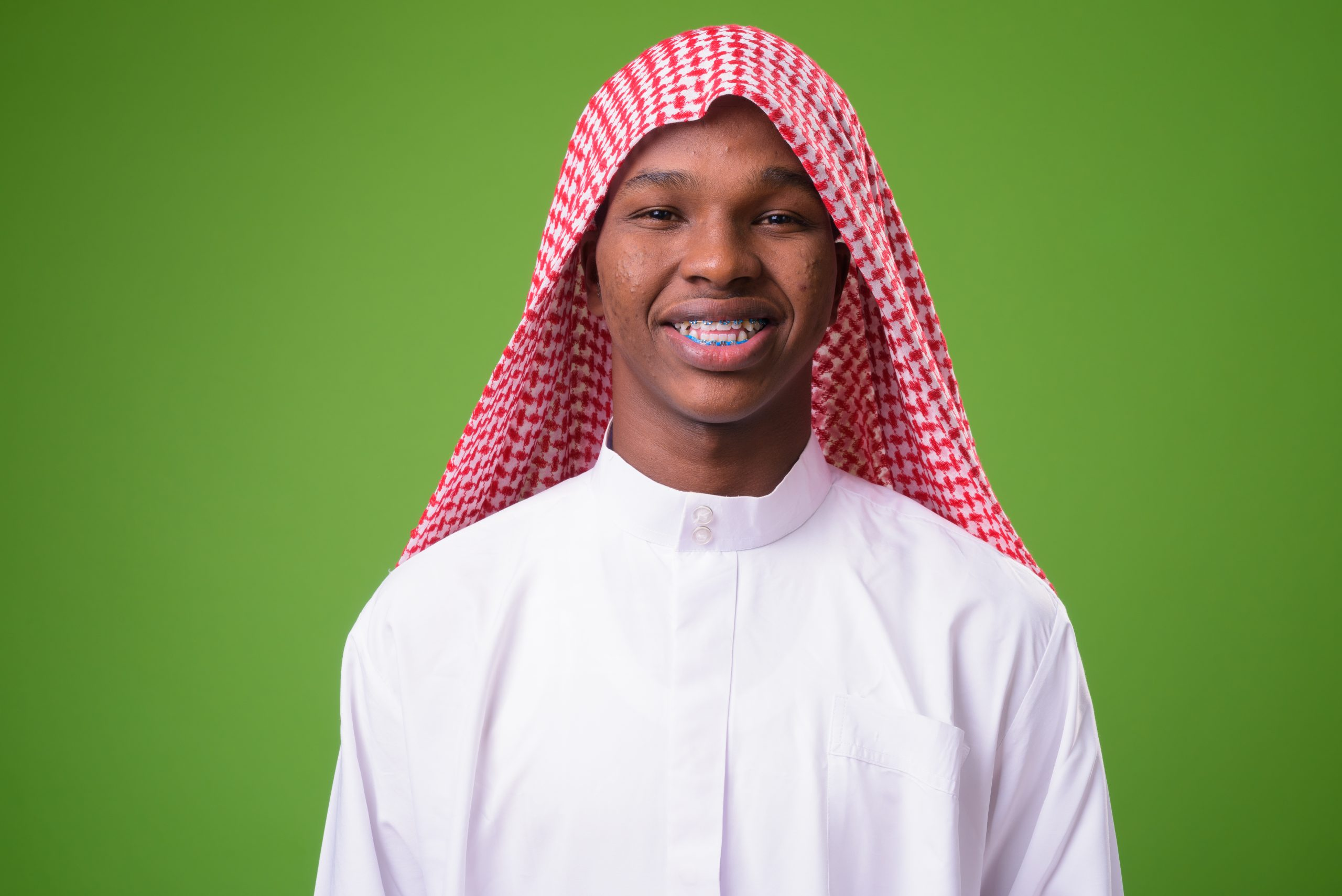 Studio shot of young African man wearing traditional Muslim clothes against green background